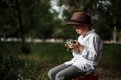 Little boy in vintage clothes sitting on a vintage suitcase with a retro camera in his hands stock photo