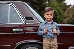 Little boy in vintage clothes standing next to retro car.  stock photo