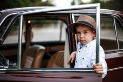 Little boy in vintage clothes stands near the retro car. Time machine royalty free stock images