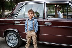 Little boy in vintage clothes stands near the retro car. Time machine royalty free stock image