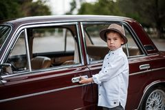 Little boy in vintage clothes stands near the retro car. Time machine royalty free stock photos