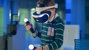 Little boy in virtual reality headset holding move motion controllers. Professional shot in 4K resolution. 093. You can use it e.g. in your commercial video stock photos