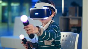 Little boy with virtual reality motion controllers having immersive gaming experience. Professional shot in 4K resolution. 093. You can use it e.g. in your Royalty Free Stock Images