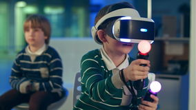 Little boy in vr headset playing virtual reality game with controllers while another boy waiting for his turn stock footage