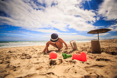 Little Boy w Kapeluszowych pełni Plastikowym kubku z piaskiem Robi tortowi na plaży Fotografia Stock