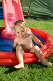 Little boy in wading pool. Little boy with a water slide in the garden Royalty Free Stock Photos