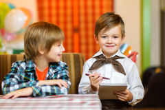 Little boy waiter accepts the order in a cafe or Royalty Free Stock Images