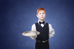 Little boy waiter stands with empty tray serving something Royalty Free Stock Photos