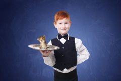 Little boy waiter stands with gray kitten on tray Royalty Free Stock Image