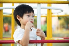Little boy waiting and looking for his parent at playgroun. Little asian boy waiting and looking for his parent at playground Stock Photo