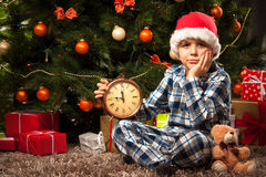 Little boy waiting for Santa. Little boy in pajama with the alarm clock waiting impatiently for Santa Stock Photography