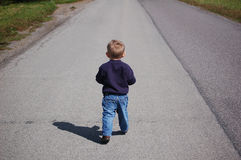 Little Boy Walking. One year old boy taking a walk on a rural road Royalty Free Stock Photos