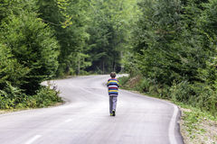 Little boy walking alone on the road in forest Royalty Free Stock Photos