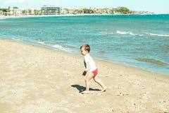 Little boy walking along the beach stock images