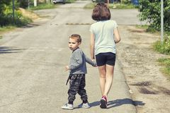 The little boy is walking along the road with his sister