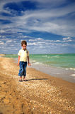 Little boy walking on the beach vertical Royalty Free Stock Photos