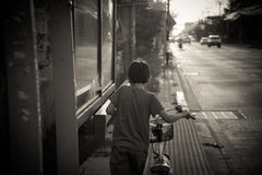 Little boy walking with bike on the street black and white Stock Images