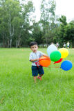Little boy walking with bruch of balloon. Asian young little boy at outdoor royalty free stock photography