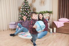 Little boy walking with christmas gift box near parents and tree royalty free stock photos