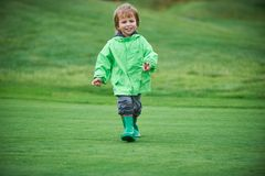 Boy walking the golf course. Little boy walking the green golf course Royalty Free Stock Photo