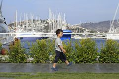 Little boy walking in a marina Stock Image