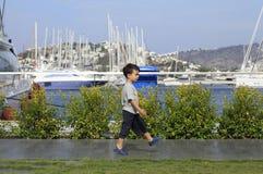 Little boy walking in a marina Stock Image