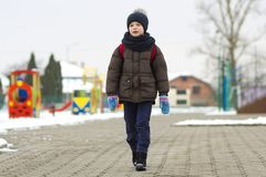 Little boy walking in the park. Child going for a walk after school with a school bag in winter. Children activity outdoors in fre. Sh air. Healthy way of life royalty free stock image