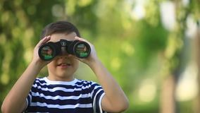 Little boy walking in the park and looking through binoculars.  stock video footage