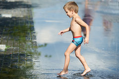 Little boy walking  in puddle Stock Photography