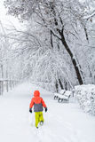 Little boy walking on snow. Kid boy walking along the road with Stock Image