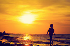Little boy walking on sunset beach Stock Photo