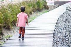 Little boy walking on thewood bridge stock image