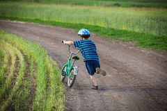 Little boy walking uphill with his bike on rural landscape Stock Photos