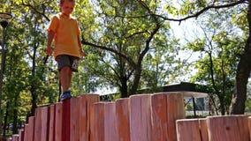 Little boy walking on wooden pillars