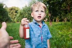 Little boy walks alone in a meadow and drinks juice Royalty Free Stock Image