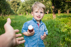 Little boy walks alone in a meadow and drinks juice Royalty Free Stock Images