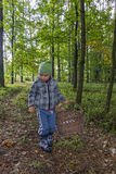 Little boy walks forest path with wicker basket Stock Photo