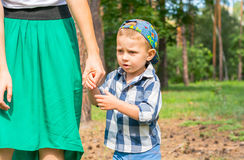 Little boy walks in the park by the hand with his mom. Family resting in the park stock image