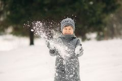 A little boy walks in the park in the winter weather, play snowballs and rejoiced. Waiting for Christmas mood stock photos