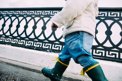 Little boy walks through the puddles in the street Stock Photography