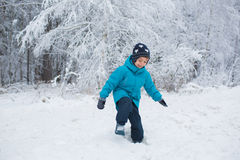 Little boy walks in a snow in the winter park. A little boy walks in a snow in the winter park Royalty Free Stock Photos