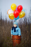 Little boy wants to fly on balloons Stock Images