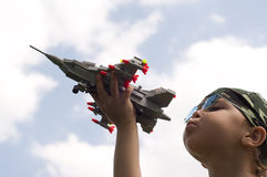 Little boy and war-plane. A little boy dreams of becoming a fighter pilot Stock Image