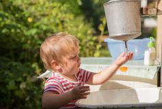 Little boy washes his hands under water dispenser Royalty Free Stock Image