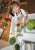 Little boy washes vegetables before eating. Little boy washes vegetables on the kitchen before eating Stock Photos