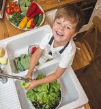 Little boy washes vegetables before eating. Little boy washes vegetables on the kitchen before eating Royalty Free Stock Images