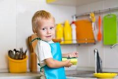 Little boy washing dishes Royalty Free Stock Photos