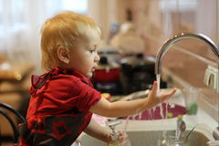 Little boy washing dishes at home Royalty Free Stock Images