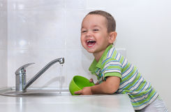 Little boy washing dishes. In the kitchen Royalty Free Stock Photo