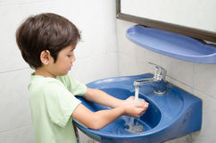 Little boy washing hand royalty free stock photography